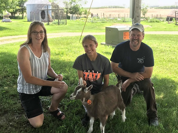 The 2018 IDGA Share-A-Kid program: Tim & Mary Schmidt of Schmidt/ECF have donated a Toggenburg doeling to Taylor McCreedy, age 14, of Cass County. Pictured left to right are Mary Schmidt, Taylor McCreedy, and Tim Schmidt, with doeling Kixify!